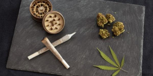 Marijuana joints, dried cannabis buds, and a marijuana leaf on a flat surface