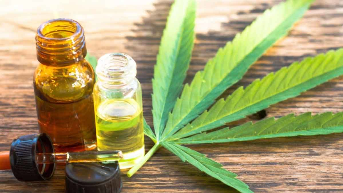 CBD oil with cannabis leaf on a wooden surface